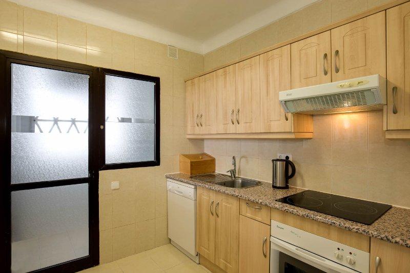 Cozinha com despensa separada atrás da porta de vidro.