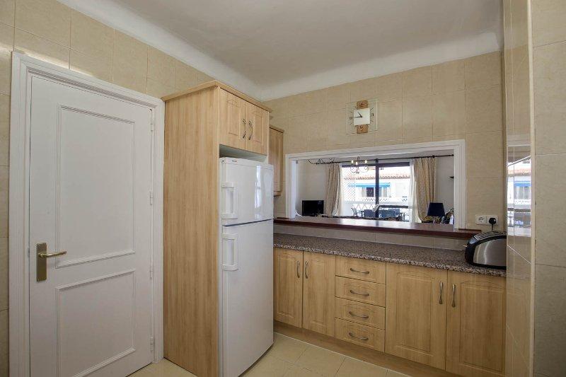 Arejado e cheio de luz área de cozinha com serviço escotilha para a área de jantar.