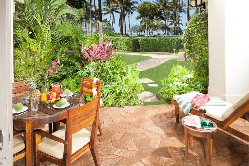 Lanai mit Meer und Blick auf den Garten. Lanai hat einen Tisch, 4 Stühle, und eine Chaiselongue.