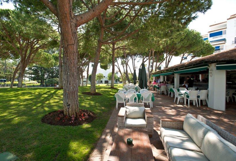 Escolha um local com sombra ou de sol no restaurante à la carte nos jardins do Playas del Duque.