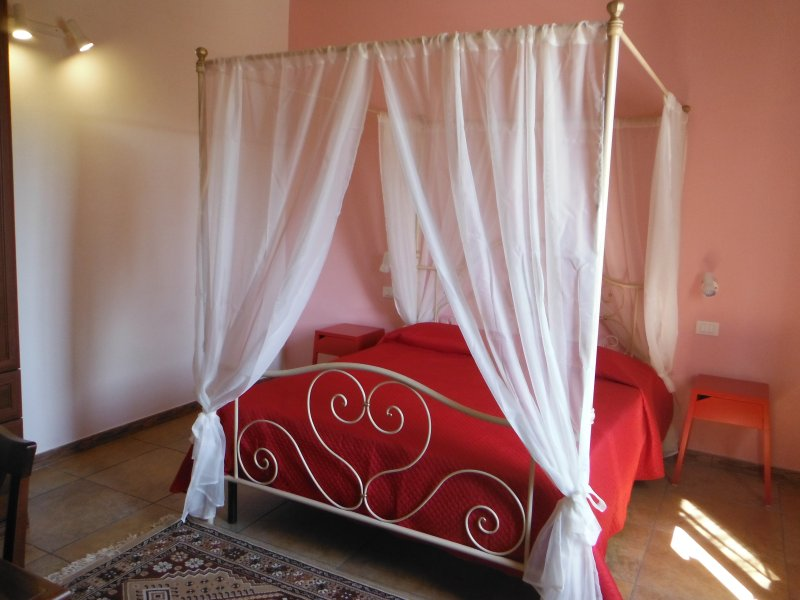 bedroom with large window, double bed, bedside tables, wardrobe, desk.