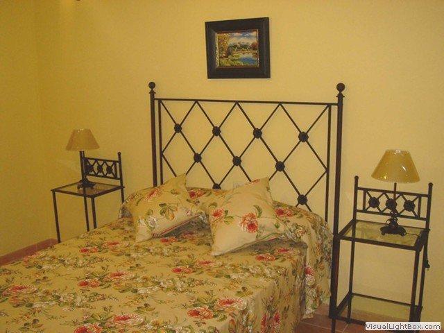 Vista parcial del dormitorio con cama de matrimonio.