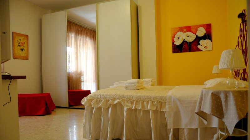 Bedroom with double bed, ottoman bed, tv and access to the balcony.