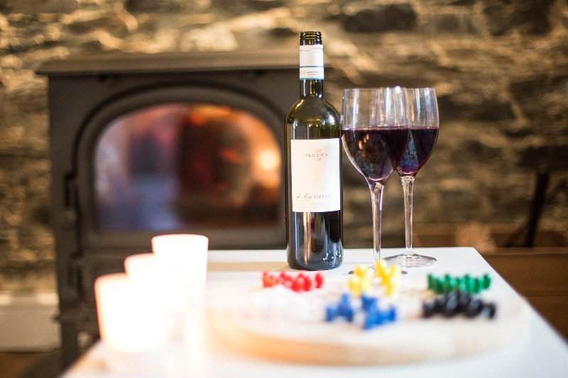 Relax with a glass of wine over a game in front of a roaring fire