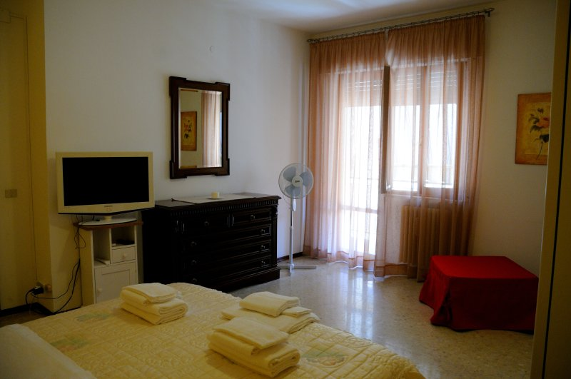 Bedroom with double bed, ottoman bed, tv and access to the balcony