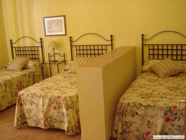 Vista parcial de dormitorio con 4 camas individuales separadas en dos ambientes.