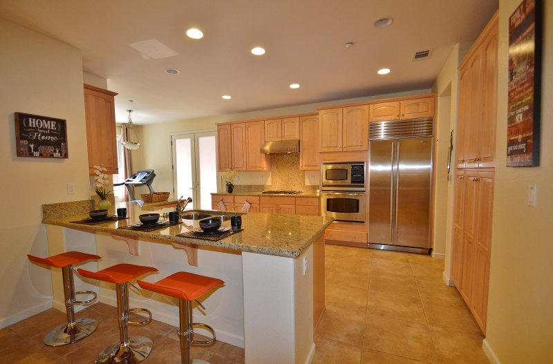 Modern kitchen- eat in kitchen, over the counter stoves, stainless steel high-end appliances.