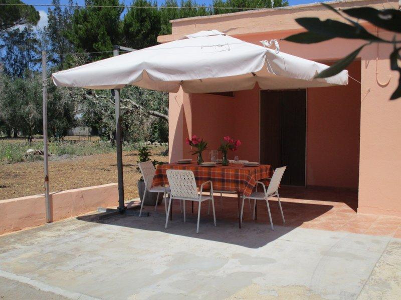 Spazio esterno attrezzato con ombrellone, tavolo e sedie