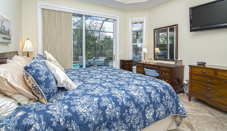First floor master bedroom with flat panel TV access to pool.