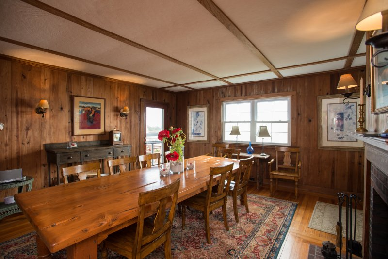 Dining room with custom made pine table and fireplace facing the water