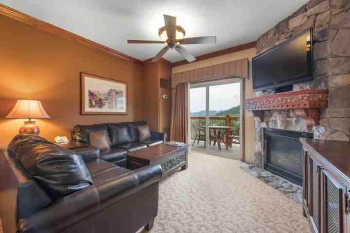 """The living room features two new leather couches, 54"""" HDTV, enhanced cable, free Wi-Fi, stone mantle and floor to ceiling stone gas fireplace."""