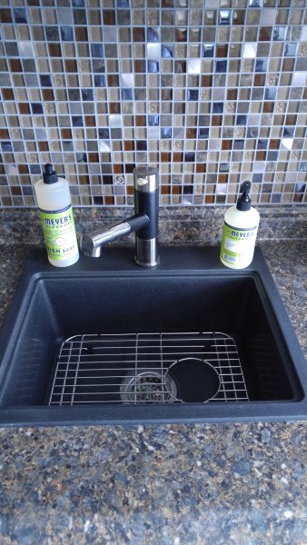 Kitchen granite sink with pull out sprayer and all Meyers Lemon Verbeane products.