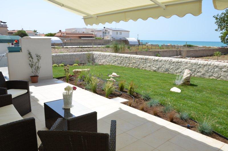 Comoda veranda con vista sul giardino e sul mare. Atmosfera accogliente la sera