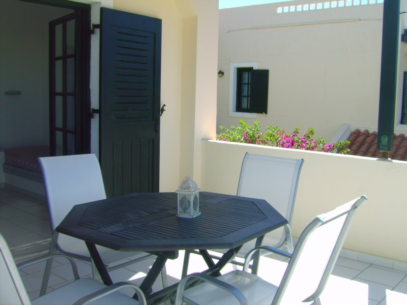 Large spacious balcony with sun loungers and dining furniture