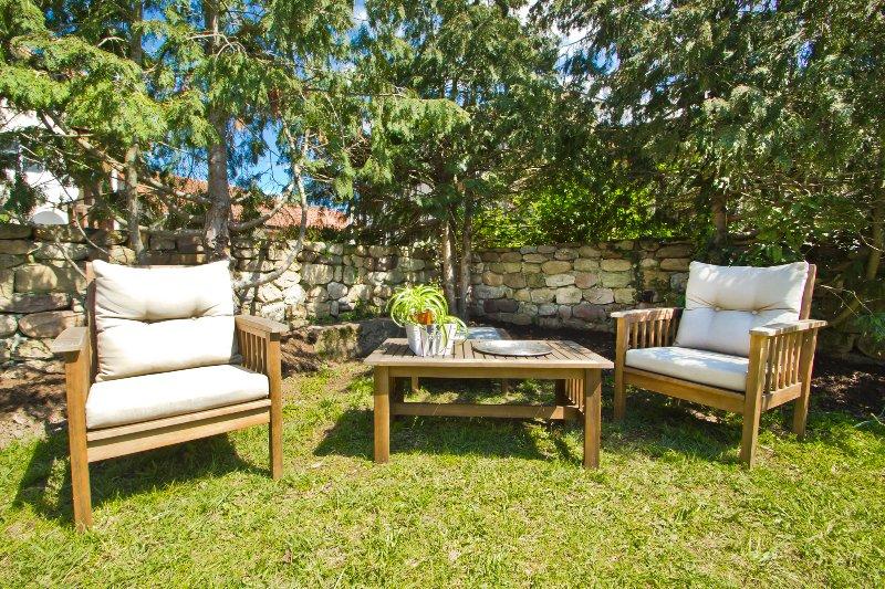 Detalle jardín con barbacoa y porche cenador.