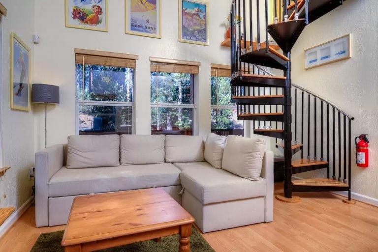 Le salon à aire ouverte a de hauts plafonds, un canapé et foyer au bois de palettes coupe confortable.