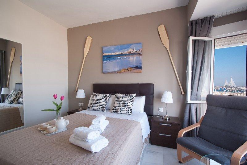 Dormitorio con vistas al mar, aire acondicionado y TV