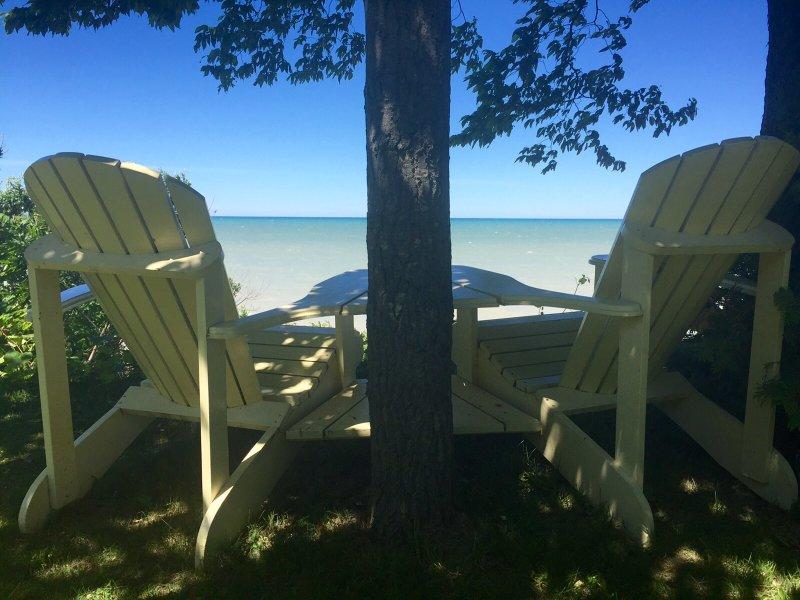 Adirondack sillas dobles que miran hacia fuera en el lago Huron