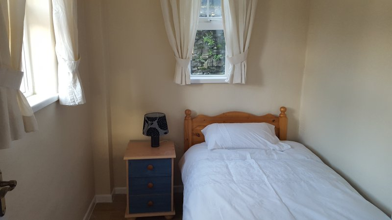 Small room located at the back of house contains single bed,wardrobe  and bedside locker