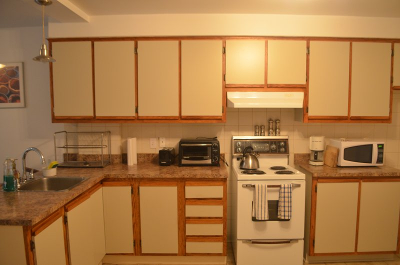 Fully equipped kitchen with pots and pans for cooking and baking.