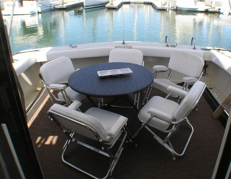 Cockpit area with dining table and 5 boat chairs.