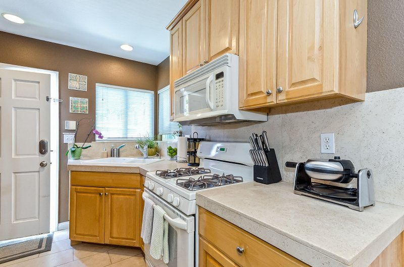 Kitchen is FULLY stocked for long-term stays: waffle maker, knives, kitchen towels all shown here.