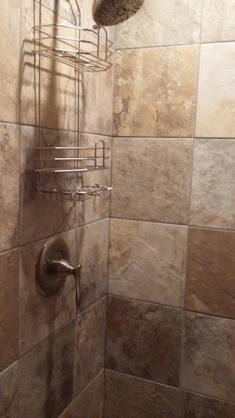 Tiled shower in lower level bathroom