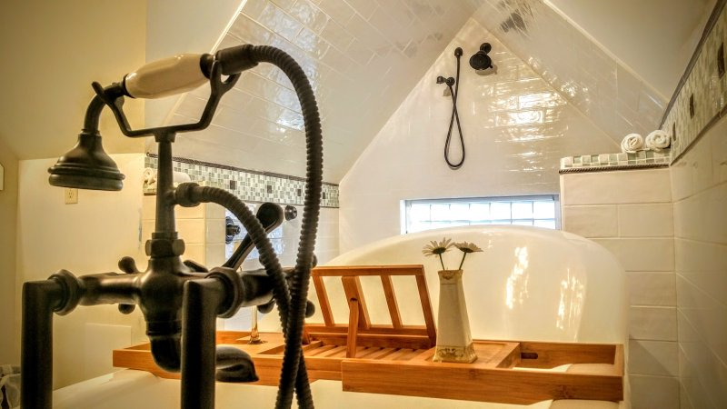 The Attic Suite bathroom has a slipper clawfoot tub & vertical spa with shower heads & body jets.