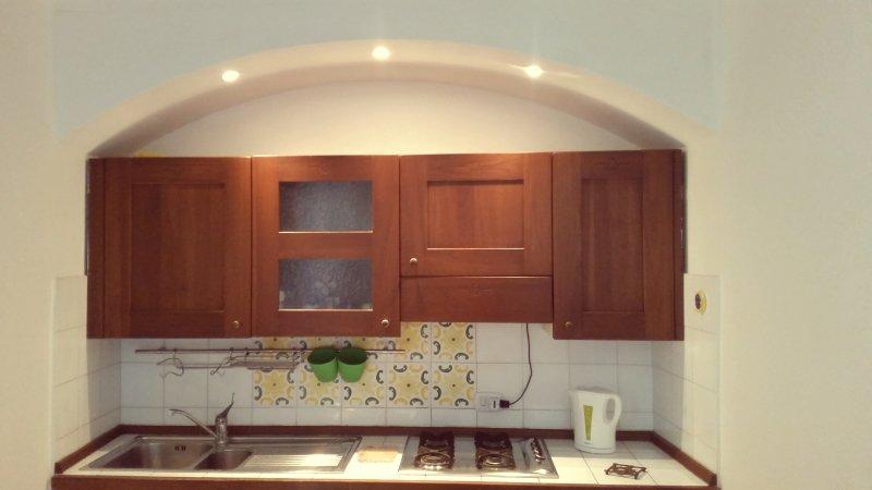 Cucina completa di lavastoviglie, frigo, microonde, bollitore e tostapane.