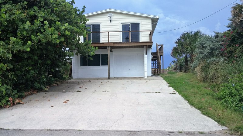 Street side of home with sunset deck and driveway parking for 4 cars. Beach is on other side