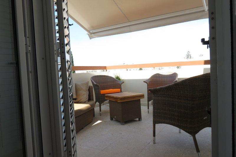 portes fenêtres avec volets persiennes donnant sur véranda