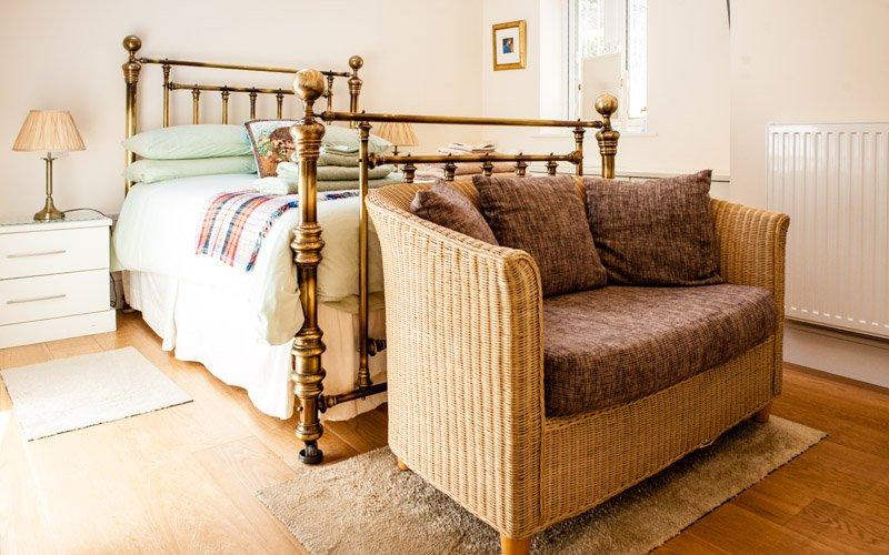 Bellotas cama de latón con armarios empotrados y cuarto de baño con ducha de lluvia y bañera de época