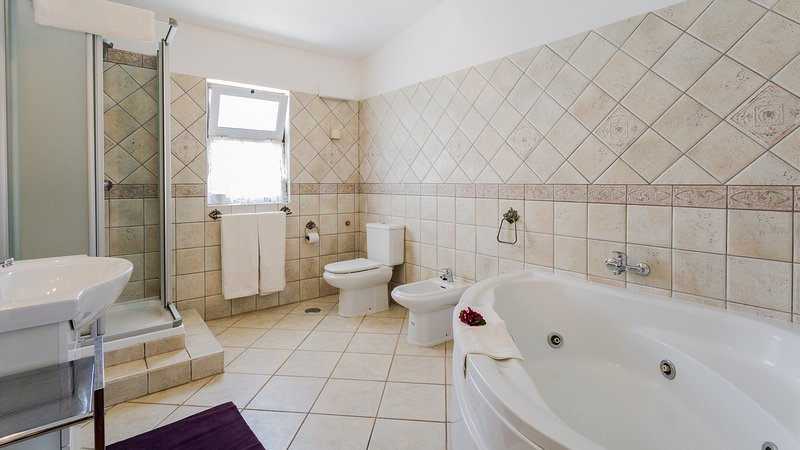 Large en suite bathroom with jacuzzi bath. Separate shower cubicle. .