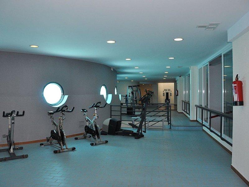 parte del gimnasio, con ojos de buey con vistas al interior de la piscina y pistas de squash