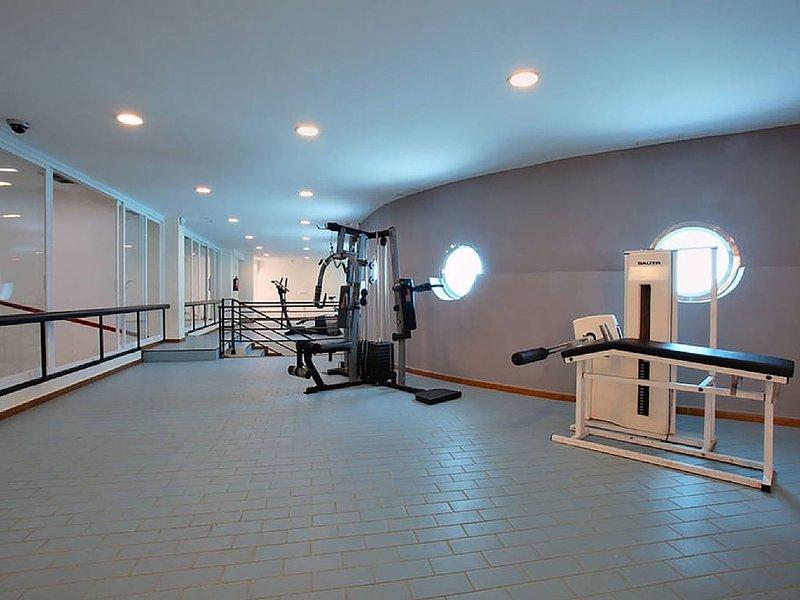 maquinas de pesas y a la izquierda pistas de squash