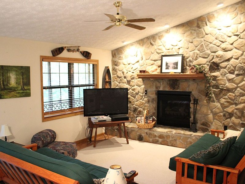 Spacious Living room, with stone wall fire place and two futons for four more people!