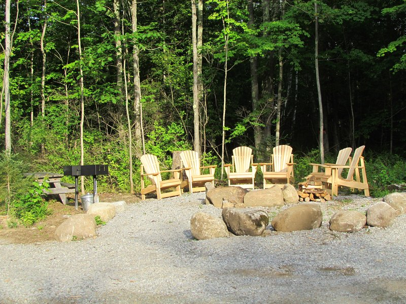 Fire pit with six Adirondack chairs, two charcoal grills, and picnic table.