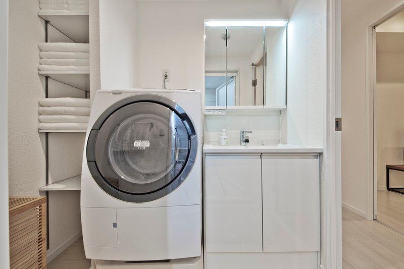 pia do banheiro com espelho de maquilhagem e lavadora / secadora