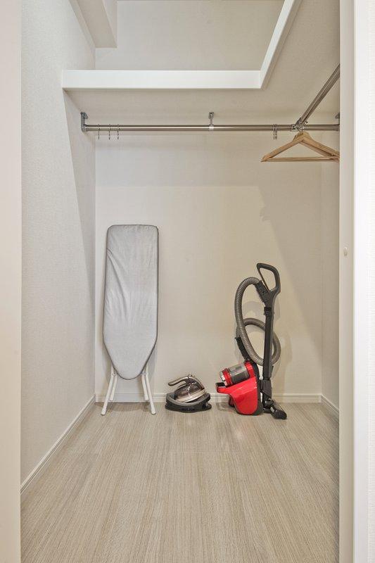 Walk-in closet com ferro, tábua de engomar e aspirador de pó