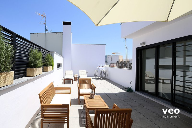 Terrace with outdoor seating and 2 deck chairs.