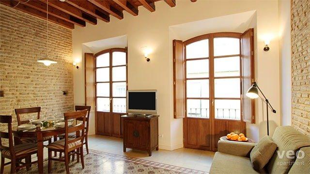 Bright living room featuring exposed brick walls, beams and original floor tiles.