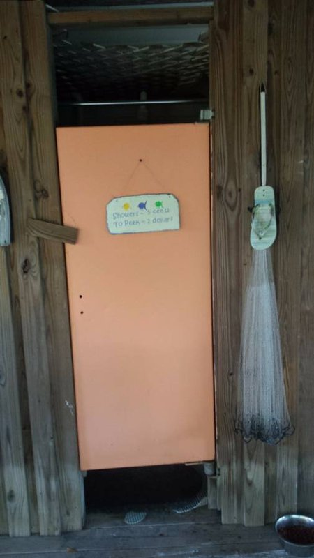 Whimsical sign on outdoor shower located on back porch.