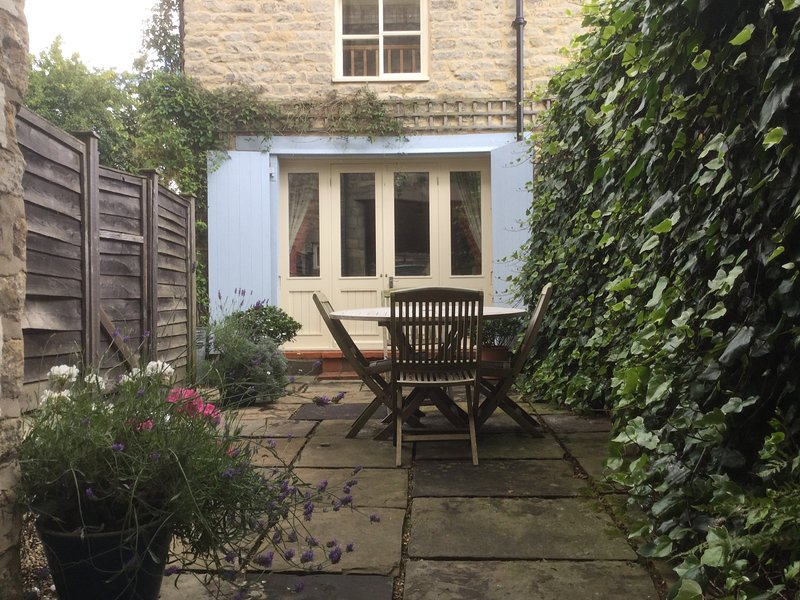 French Windows lead out to a pretty courtyard with seating area at the front of the cottage.
