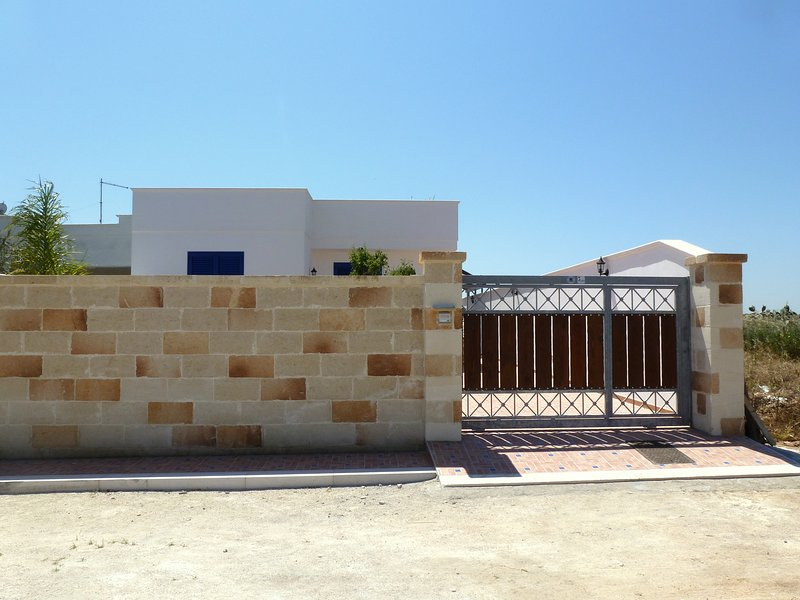 Natural stone entrance wall with timber gateway into Villa Azzurra