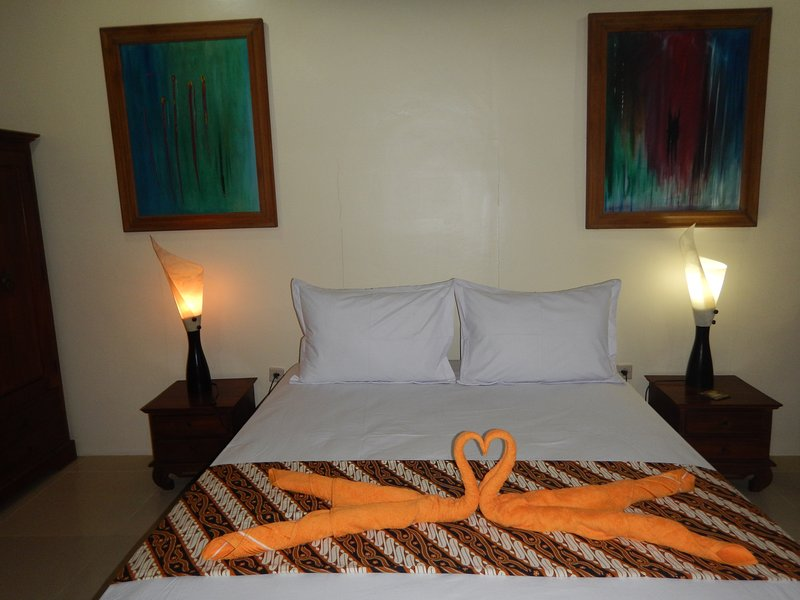 Queen sized teak bed with teak bedside tables. Paintings by Jana!