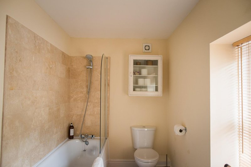 Bathroom with bath and shower over, loo and washbasin. Plump towels provided.