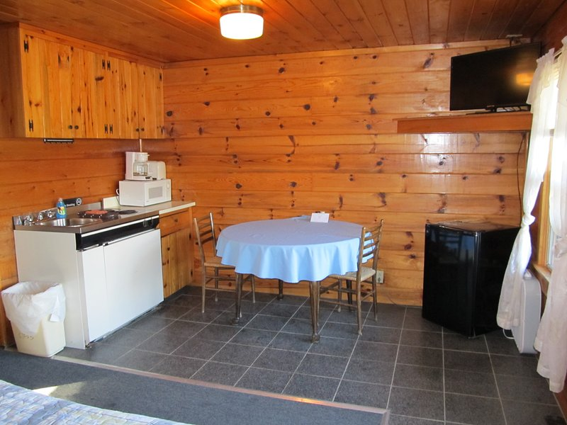 Kitchenette with cook top, small refrigerator, microwave and flat screen TV.