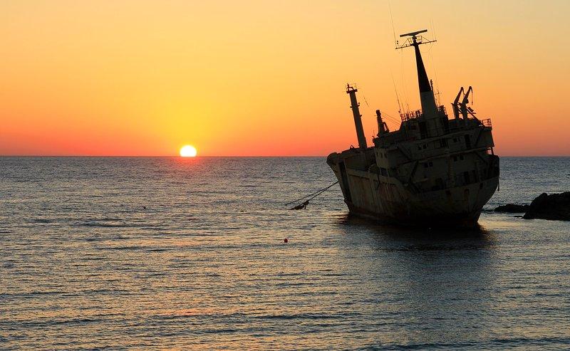 Puesta del sol sobre naufragio en el mar Cuevas