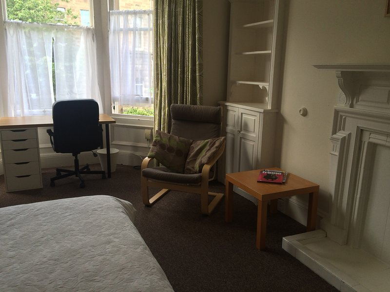 Large double bedroom with easy chair, desk and coffee table overlooking tree-lined street