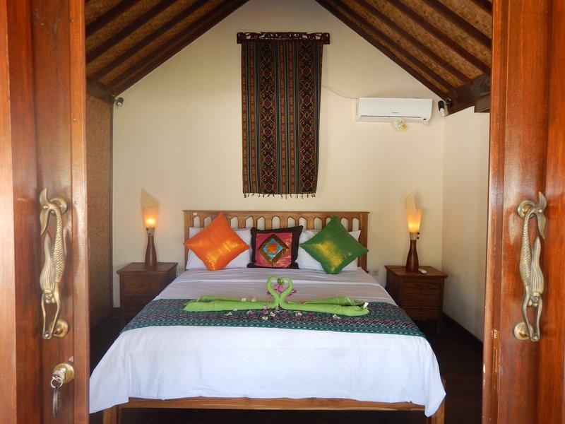La sala sasak re ha esposto soffitto a volta con motivi balinesi e un letto king size.